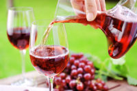 Pouring red wine from decanter with grapes on background - Selective focus- XXXL Image